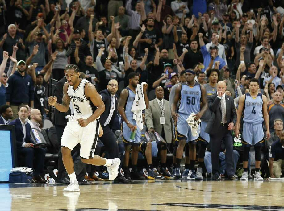 Spurs' Kawhi Leonard (02) reacts in front of the Memphis Grizzlies' bench after hitting a clutch jumper that tied the game late in regulation of the Spurs' 95-89 triumph over the Grizzlies at the AT&T Center on Tuesday, Apr. 4, 2017. (Kin Man Hui/San Antonio Express-News) Photo: Kin Man Hui,  Staff / San Antonio Express-News / ©2017 San Antonio Express-News