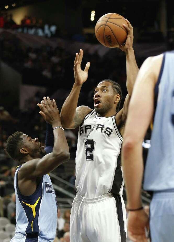 Spurs' Kawhi Leonard (2) takes a shot against the Memphis Grizzlies' James Ennis, III (8) on April 4, 2017. Photo: Kin Man Hui /San Antonio Express-News / ©2017 San Antonio Express-News