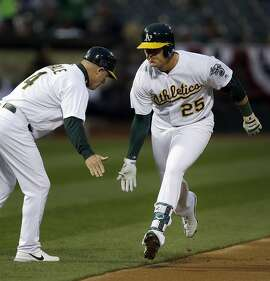Oakland Athletics' Ryon Healy, right, celebrates with third base coach Chip Hale after hitting a home run off Los Angeles Angels' Matt Shoemaker in the first inning of a baseball game Tuesday, April 4, 2017, in Oakland, Calif. (AP Photo/Ben Margot)