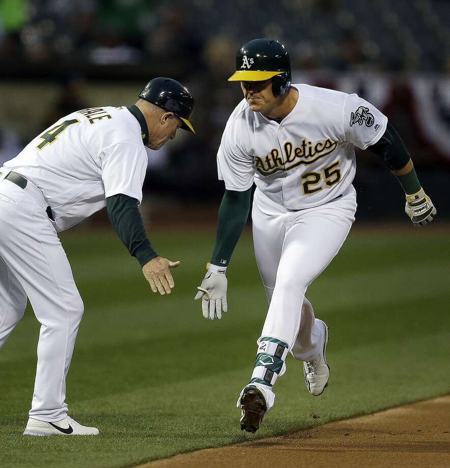Oakland Athletics' Ryon Healy, right, celebrates with third base coach Chip Hale after hitting a home run off Los Angeles Angels' Matt Shoemaker in the first inning of a baseball game Tuesday, April 4, 2017, in Oakland, Calif. (AP Photo/Ben Margot) Photo: Ben Margot, Associated Press