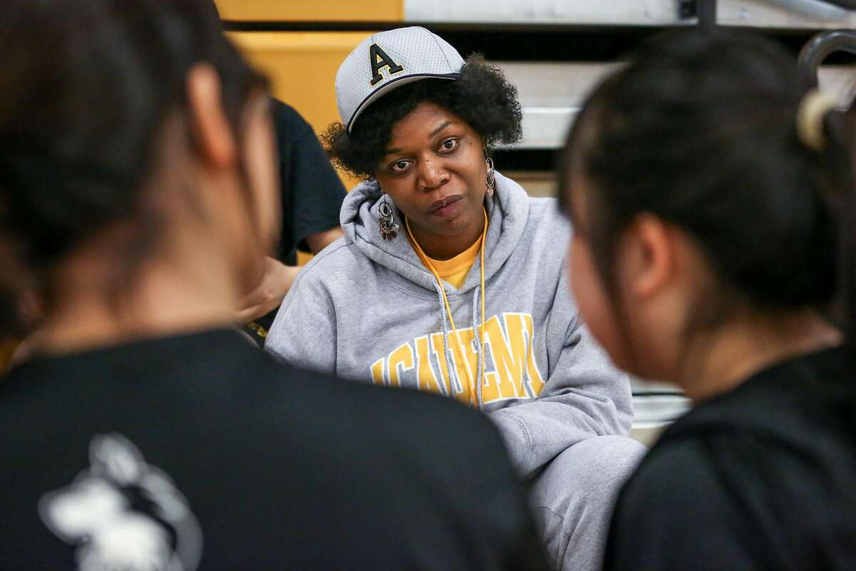 Math teacher and badminton coach Etoria Cheeks listens as students tell her about their badminton match at The Academy San Francisco high school on Tuesday, April 4, 2017 in San Francisco, Calif.