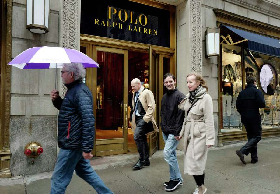 People pass the Polo Ralph Lauren store on Fifth Avenue, Tuesday, April 4, 2017, in New York. Ralph Lauren Corp. said that it is shuttering the high-profile store less than three years after opening it. The closure is part of the New York fashion company's plan to save $140 million annually. The company said it will close other stores, cut jobs and shut some corporate offices, but did not provide details. (AP Photo/Mark Lennihan) ORG XMIT: NYML104 Photo: Mark Lennihan / Copyright 2017 The Associated Press. All rights reserved.