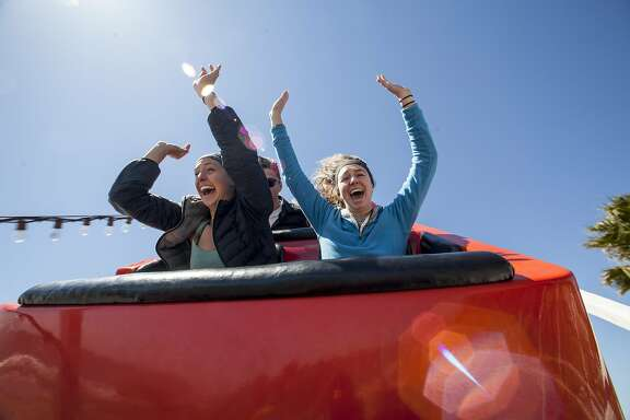 Riders go hands-free during one of the drops on the Giant Dipper at the Santa Cruz Beach Boardwalk.
