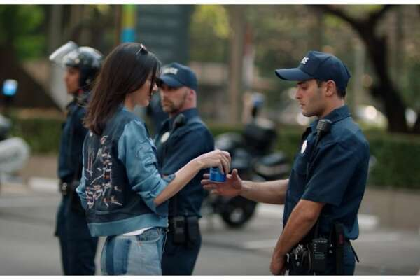 """Here it is! Ms. Jenner hands a patrolling officer a can of Pepsi (make sure you clock that police officer in the background on the left, whose flipped-up motorcycle helmet visor can sublimate police riot gear without requiring the stones to actually use it in your commercial). This image calls as far back to the iconic Flower Power photo of a carnation in the barrel of a gun during a Vietnam war protest in 1967, right up to Ieshia L. Evans, who was detained by police in Louisiana for peacefully protesting the close-range shooting of Alton Sterling by two cops.  Perhaps more insidious is the unforgettable, self-congratulatory """"bro!"""" face of the cop who just took a Pepsi from Kendall Jenner:"""