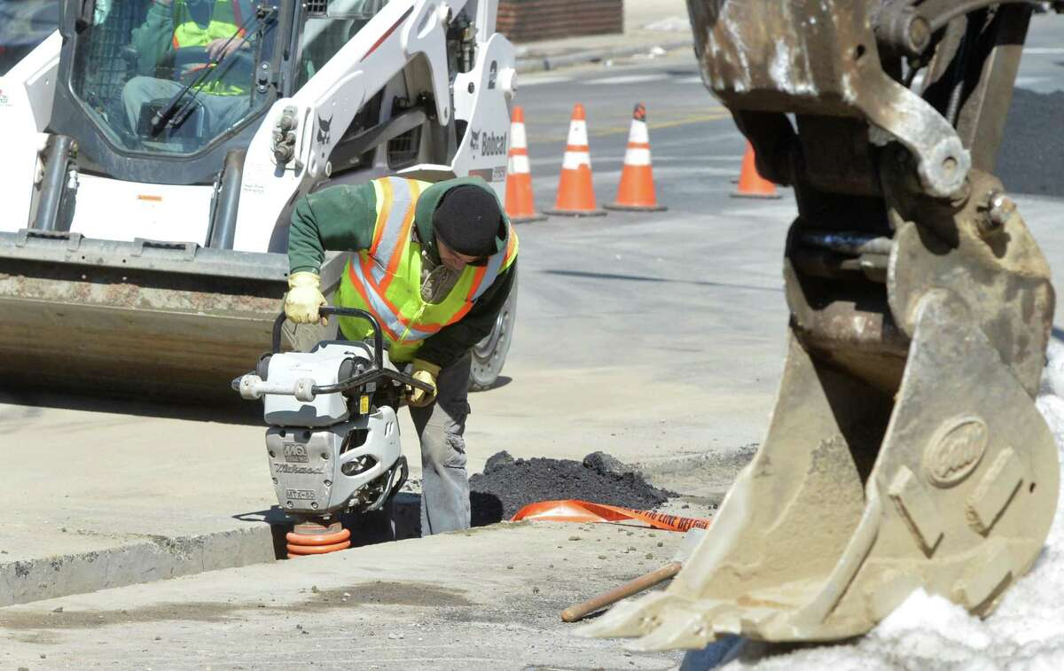 A worker with McAllen Construction works in March 2017 on a new sub-street conduit on Wall Street in Norwalk Conn.