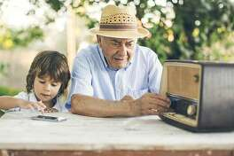 Small kid listening music from a smart phone while his grandfather from an old radio