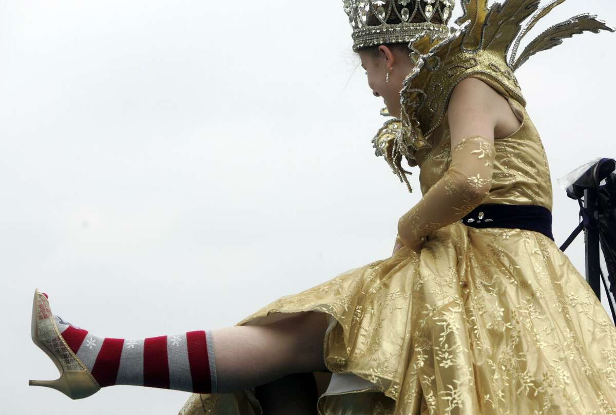 Chelsea Crain, Queen for the 50th Anniversary San Antonio Lutheran Coronation Court of Gold, shows her shoes along Santa Rosa Street near the end of the Battle of Flowers Parade in 2009.