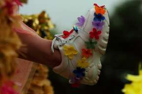 A rider on the Miss Fiesta float shows her shoes during the Fiesta Battle of Flowers Parade April 20, 2004.