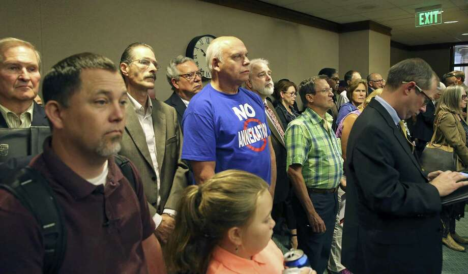 Mike Kantor stands with his no annexation t-shirt as supporters of limitations on municipal expansion crowd into the back of the room as Senator Donna Campbell, R-New Braunfels,  presents SB 715 to the Senate Intergovernmental Relations Committee at the Capitol on April 5, 2017. Photo: Tom Reel, Staff / San Antonio Express-News / 2017 SAN ANTONIO EXPRESS-NEWS