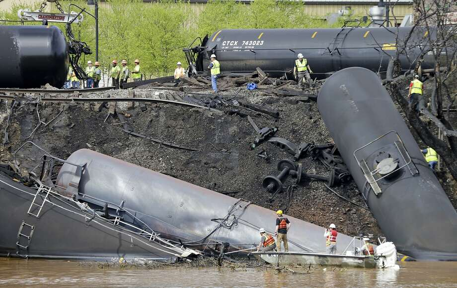 Workers remove damaged tanker cars along the tracks where several carrying crude oil derailed and caught fire along the James River near downtown Lynchburg, Va., in 2014. Photo: Steve Helber, Associated Press