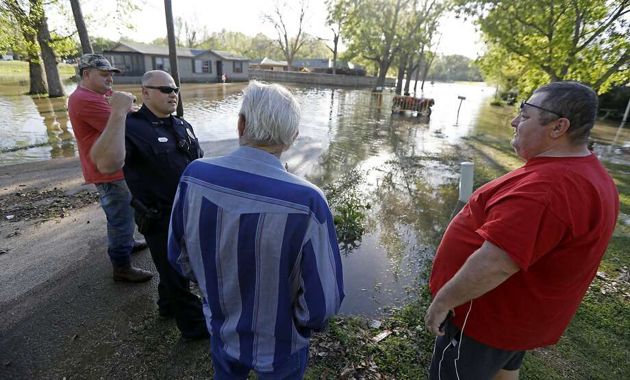 A police officer speaks with residents about the flooding in their neighborhood, in Pelahatchie, Miss. after severe storms. Photo: Rogelio V. Solis, Associated Press