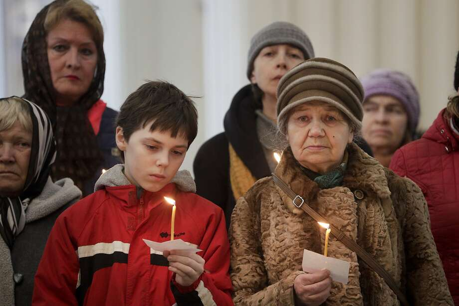 Mourners hold candles during a service at a cathedral in St. Petersburg for victims of a subway explosion. Photo: Dmitri Lovetsky, Associated Press