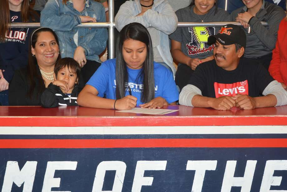 Plainview's Alondra Fraire, center, signs a letter of intent Wednesday to play volleyball at Western Texas College in Snyder. She is flanked by her mom Imelda, left, holding her 3-year-old brother Jesus, and her dad Manuel, right. Photo: Skip Leon/Plainview Herald