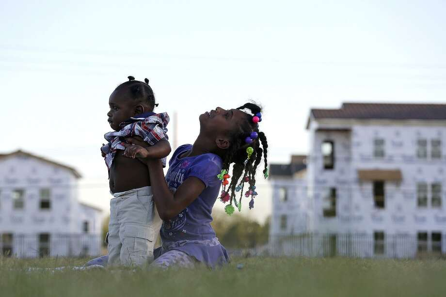 Sariyah Sheppard, 8, plays with Ge'ion Jennings, 6 months, on the field at Wheatley Middle School across from the East Meadows apartment complex under construction on March 31, 2016. Photo: Lisa Krantz / SAN ANTONIO EXPRESS-NEWS / SAN ANTONIO EXPRESS-NEWS