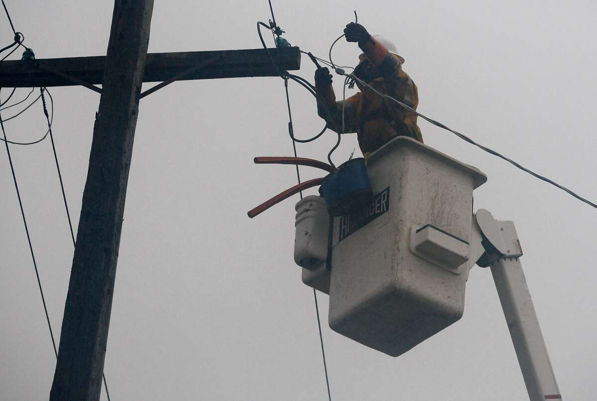 A PG&E crew restores power to two homes on Cedar Street after a large branch fell on service lines during the first major storm of the season in Berkeley on Tuesday.