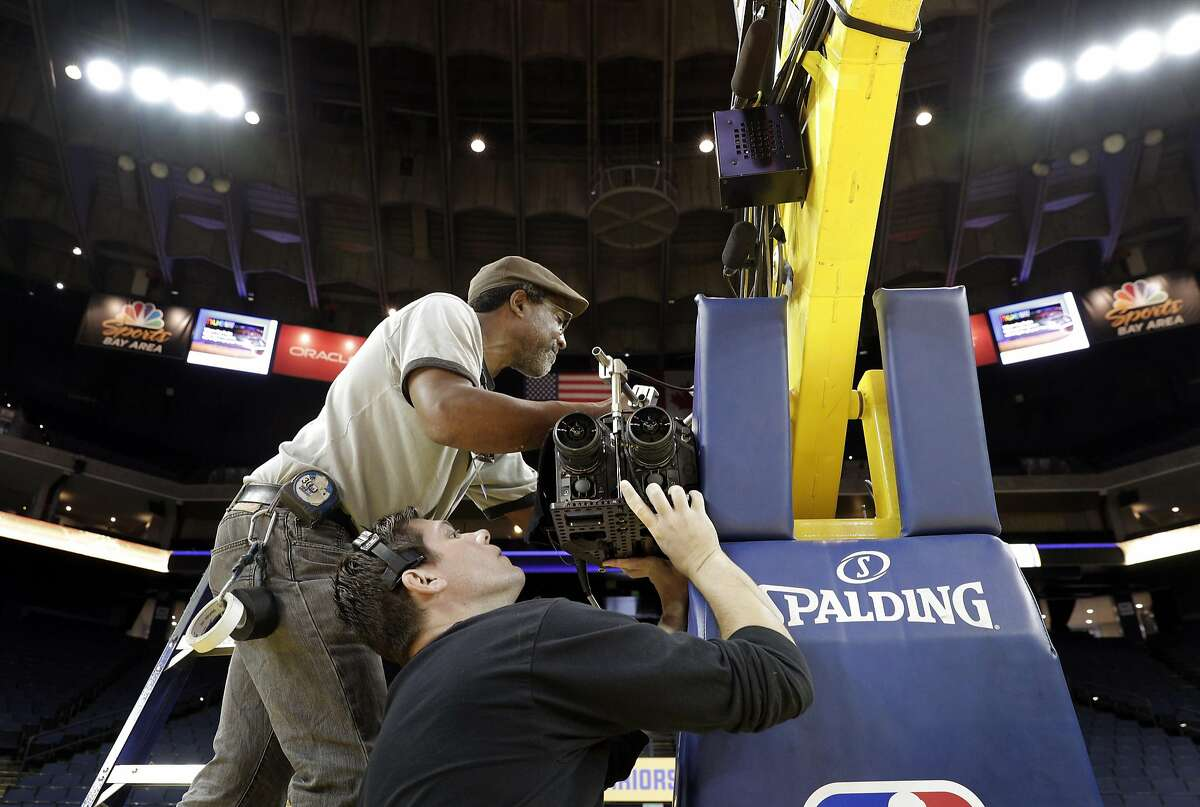 VR Director of Photography, Matt Klamm, bottom, and Don Henderson, camera rigger, set up a set of VR cameras on one of the basket stanchions before the Golden State Warriors played the Minnesota Timberwolves at Oracle Arena in Oakland, Calif., on Tuesday, April 4, 2017. NextVR, which is working on beaming live sporting around the world in VR, is broadcasting Tuesday night's Warriors game from Oracle Arena. That includes a special production truck outside, with seven VR cameras court side and elsewhere, with a dedicated announcing crew.