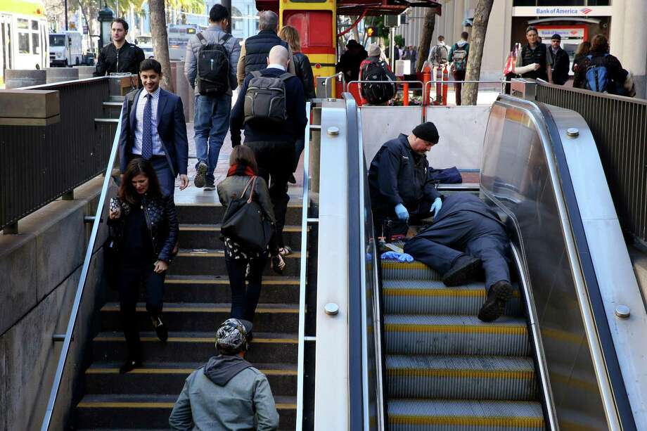 Workers fix an escalator at the Embarcadero Station in January. Broken escalators are cited in a suit against BART. Photo: Santiago Mejia / Santiago Mejia / The Chronicle / ONLINE_YES