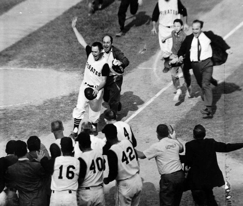 ADVANCE FOR WEEKEND EDITIONS OCT. 14-15--FILE--Fans run onto the field to mob Pittsburgh Pirates' Bill Mazeroski as he came home on his ninth-inning home run that gave the 1960 World Series to Pittsburgh, four games to three over the New York Yankees, Oct.13, 1960. (AP Photo/Harry Harris) Photo: HARRY HARRIS, Associated Press