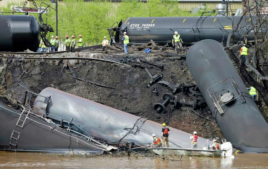Workers in 2014 inspect CSX oil tanker cars that derailed along the James River in Lynchburg, Va. Photo: Steve Helber, STF / Copyright 2017 The Associated Press. All rights reserved.