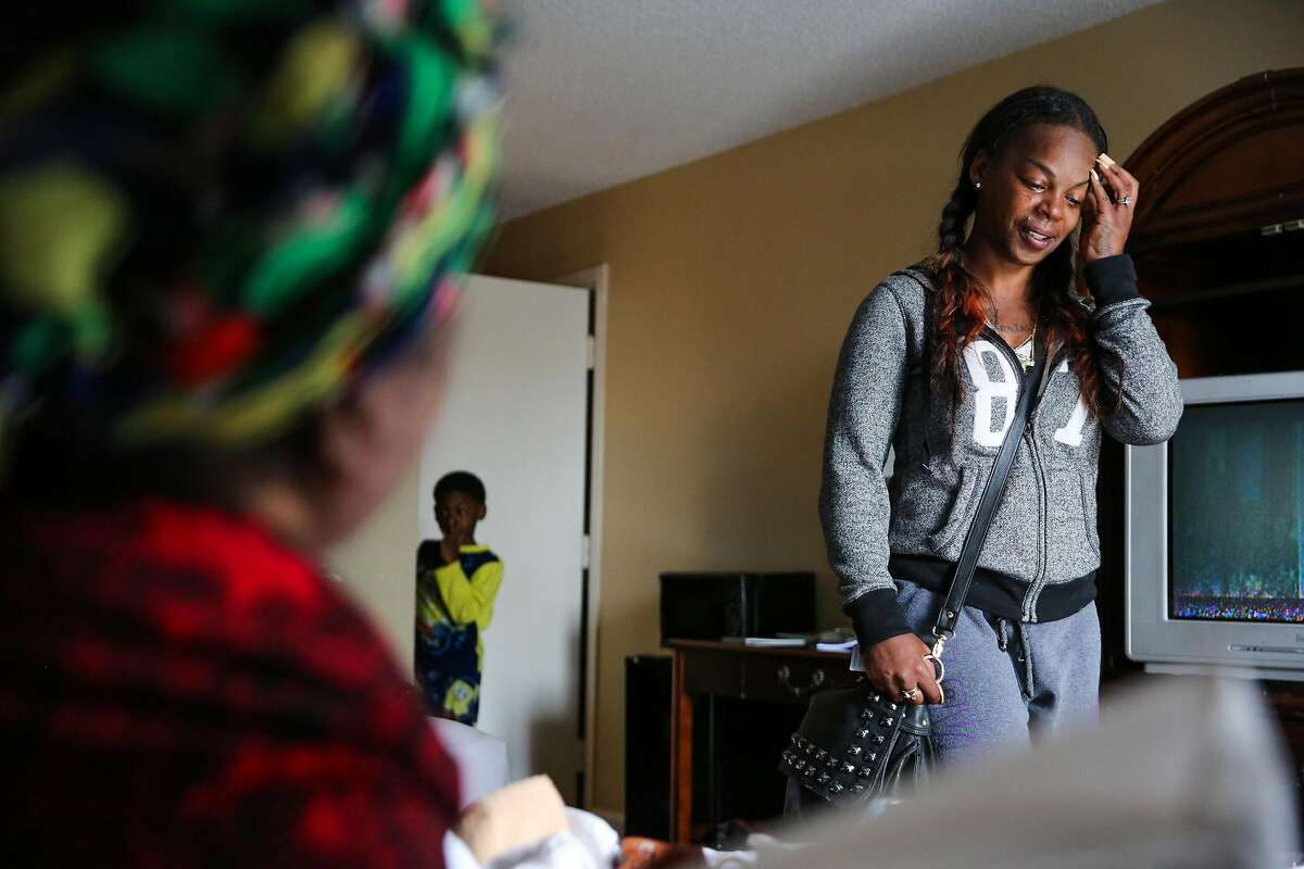 Displaced resident Kim Usher (right) gets emotional while talking to her mother Roberta Williams (left) as she walks into their new hotel room for the first time at the Jack London Inn in Oakland, California, on Wednesday, April 5, 2017. Kim and her family lost their home in a fire on San Pablo Avenue last week. Her son Million Smith, 8 (center) is also seen.