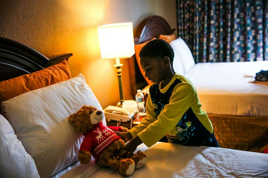 """Million Smith, 8, displaced in the West Oakland fire, sets down his teddy bear, Mr. James, at his family's temporary """"new home"""" at the Jack London Inn. Photo: Gabrielle Lurie, The Chronicle"""