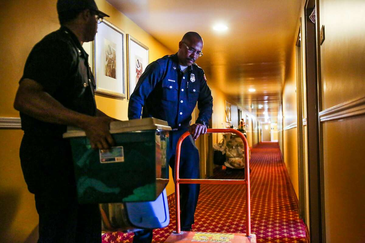 Oakland Fire official Travis Nelson (right) and his colleague (declined name) unload the belongings of displaced resident Kim Usher and her family into their room at the Jack London Inn, in Oakland, California, on Wednesday, April 5, 2017. The last few displaced residents from a fire in a building on San Pablo Avenue are being forced to move out of the Red Cross shelter that was set up at the West Oakland Youth Center.