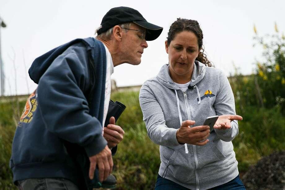 Rebecca Johnson, co-coordinator of the California Academy of Sci ences program, shows Mark Dunlop how to use the BioBlitz app. Photo: Mason Trinca, Special To The Chronicle