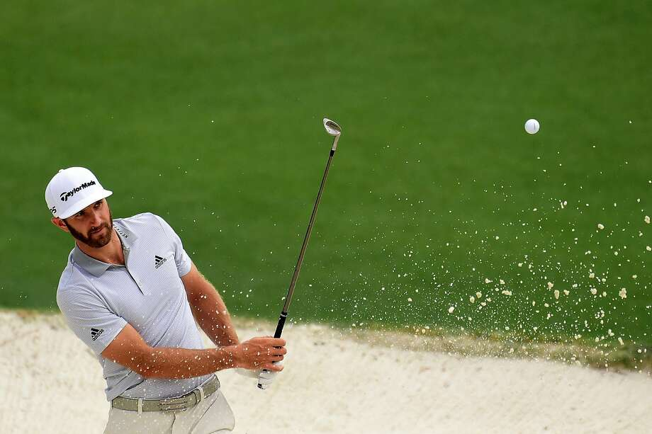 Dustin Johnson works out of a bunker during a practice round at Augusta National Golf Club. A few hours later, the world's No. 1 player would hurt his back at his rental home. Photo: Harry How, Getty Images