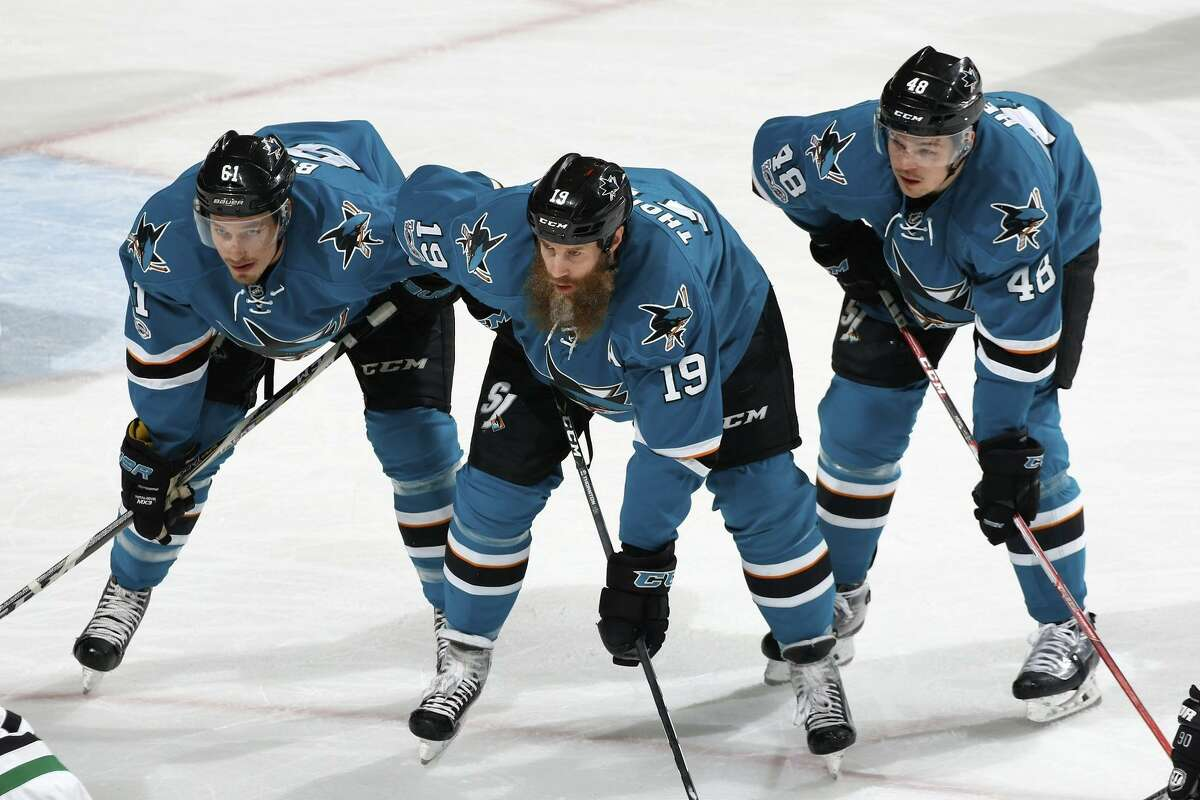 Sharks center Joe Thornton (19) - with Justin Braun (left) and Tomas Hertl - says he has no doubt he'll be able to play when the postseason begins. He played 202 straight regular-season games before hobbling away (below) with a knee injury Sunday.