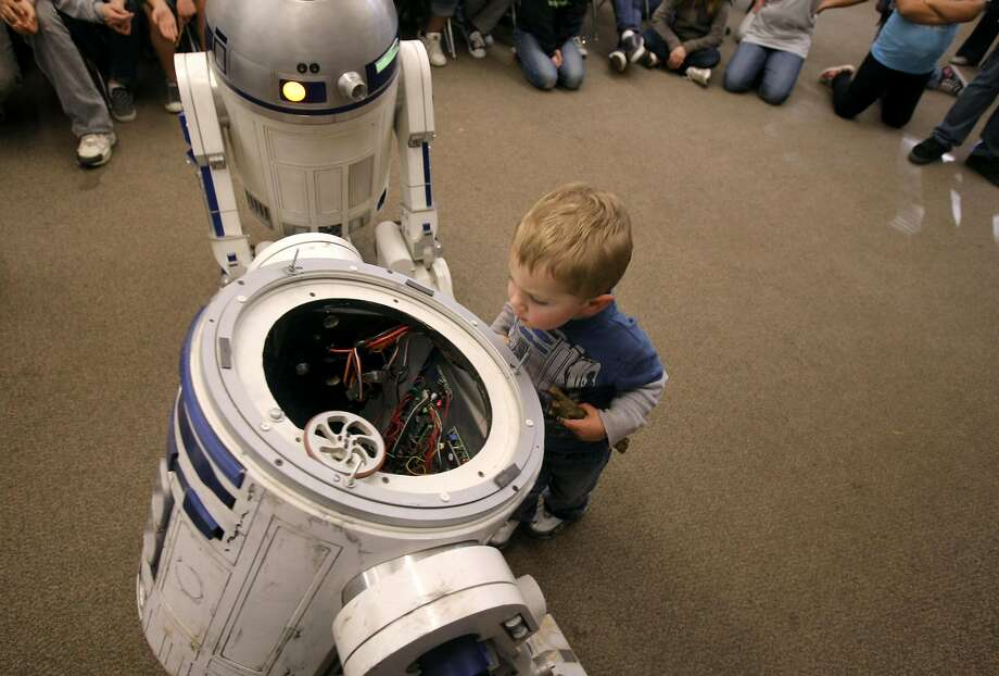 Johnathan Burton Jr. peaks inside for a glimpse of the inner workings of a R2D2 droid during a presentation at River Charter School. Photo: Thomas Levinson, The Chronicle