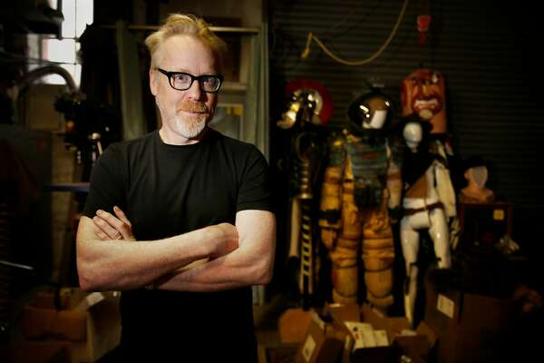 Adam Savage of Mythbusters poses for a portrait with a light saber at his workshop with some spacesuit costumes seen behind him on Monday, February 22, 2016 in San Francisco, California.
