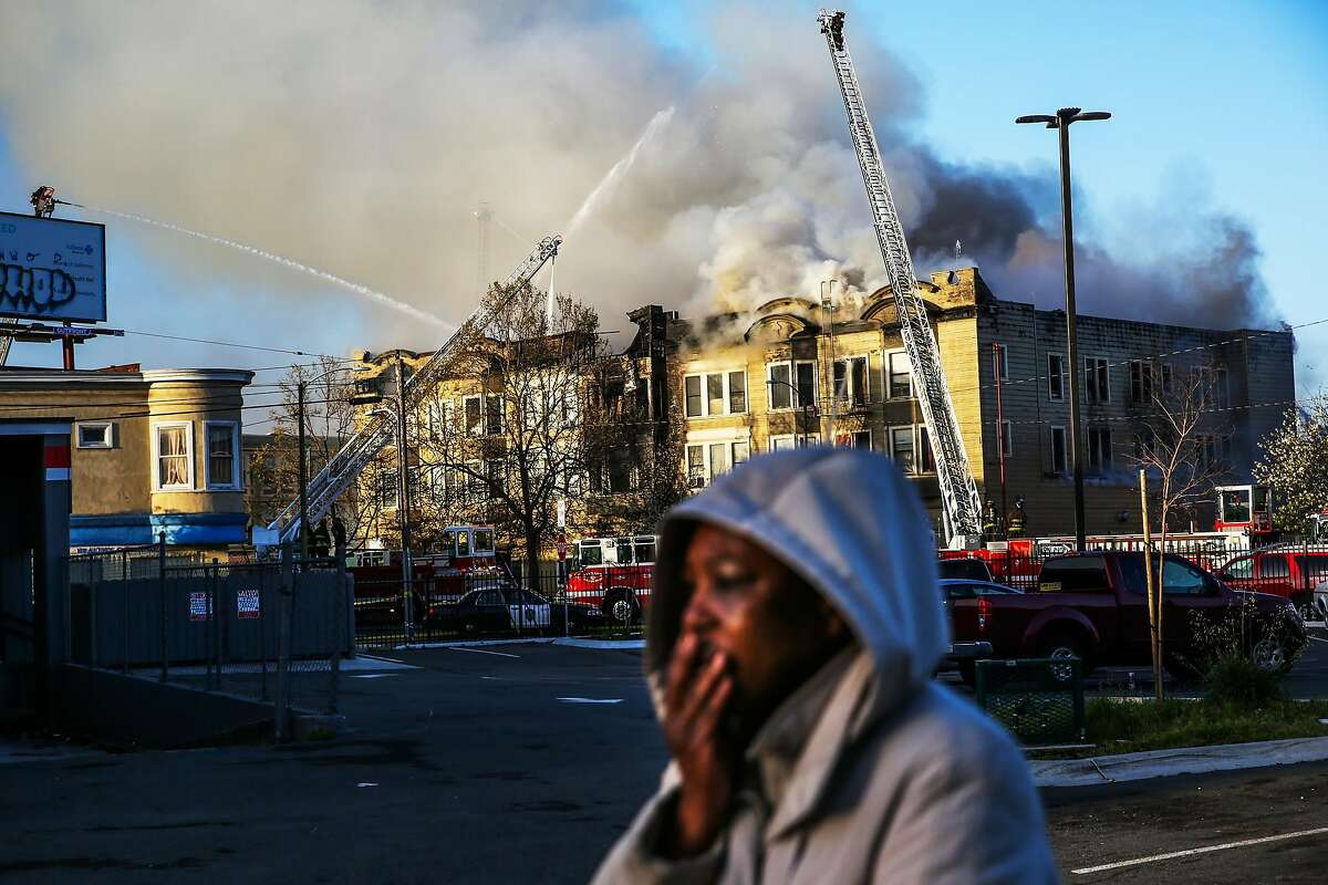 A woman gets emotional while firefighters battle an apartment building fire on San Pablo Ave. on Monday, March 27, 2017, in Oakland, Calif.