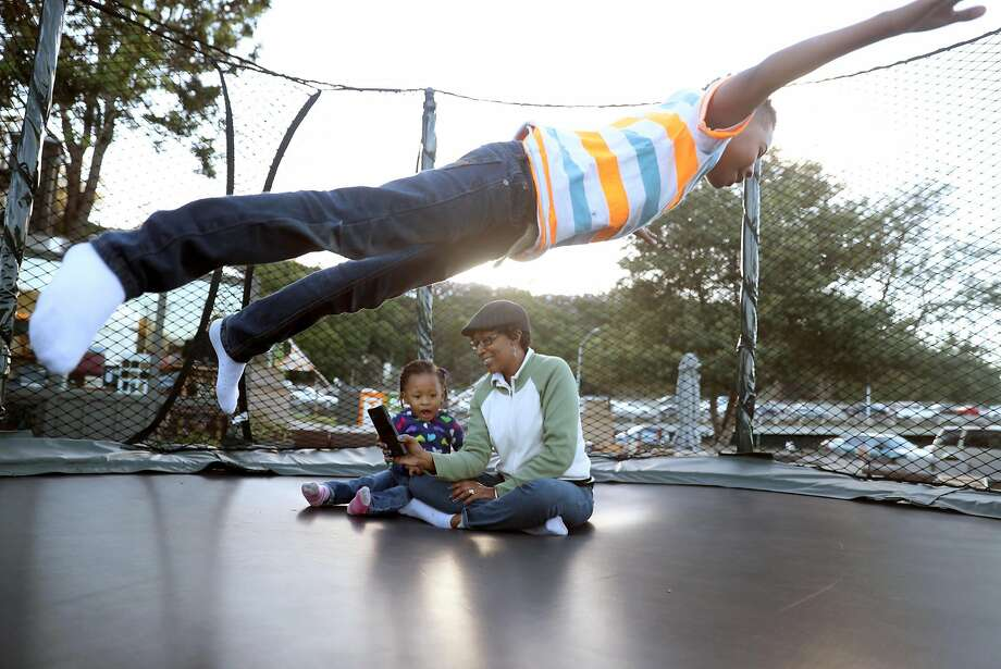 While taking a walk, Nicole Gardner-Lewis and her children, Nicholas, 8, and Amauriana, 2, stop to play in a trampoline at Terra Patio in Mill Valley, Calif., on Wednesday, November 16, 2016. Gardner'sdaughter, Ronique Gardner-Williams, was shot and killed in a drive by shooting in Richmond on December 3. 2015. Photo: Scott Strazzante, The Chronicle