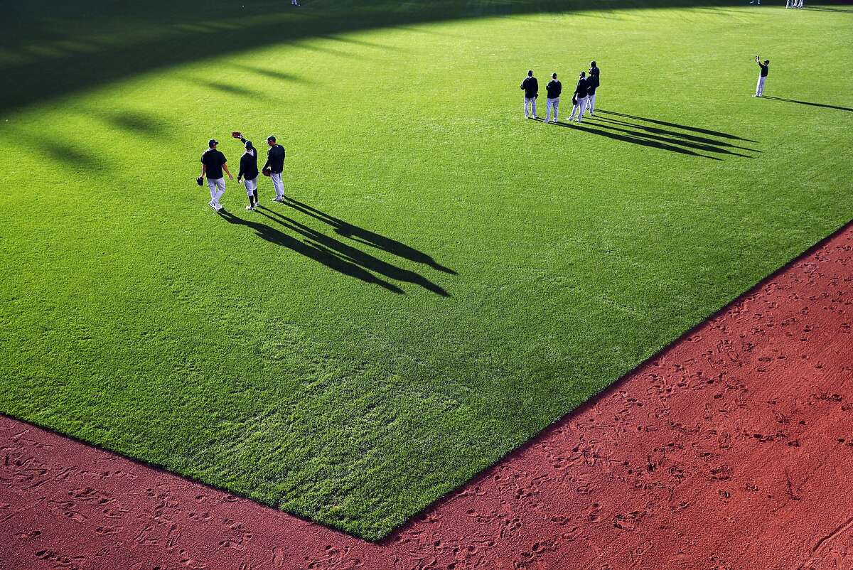 Oakland Athletics' players stand in outfield during batting practice before playing San Francisco Giants during Bay Bridge Series at AT&T Park in San Francisco, Calif., on Friday, March 31, 2017.