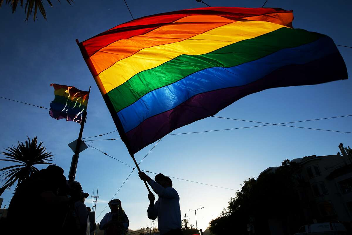 Tre Allen waves the rainbow flag in the Castro during a memorial for Gilbert Baker on Friday, March 31, 2017, in San Francisco, Calif. The memorial was for Baker, who designed the rainbow flag. Friends said Baker, age 65, died Thursday in his sleep at his home in New York. The rainbow flag has since become a symbol of the LGBT community recognized worldwide ?' celebrated at pride festivals, brandished at protests and raised every morning at the corner of Castro and Market streets.