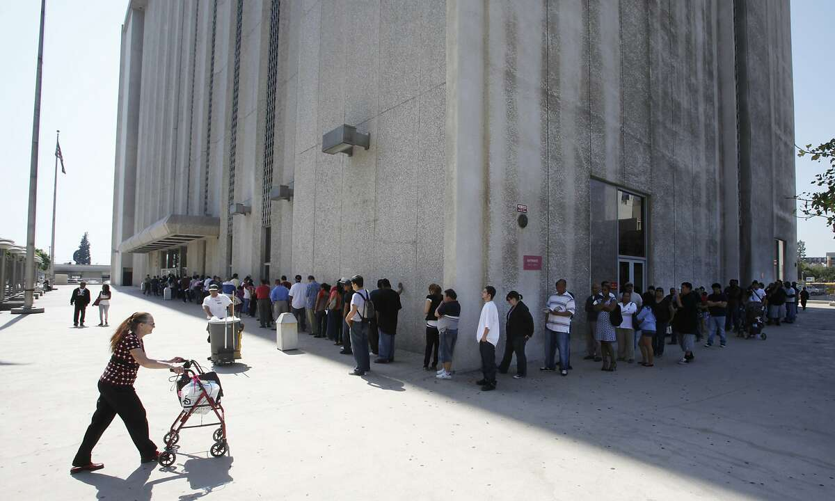 In this March 18, 2010, file photo, people line up outside the Metropolitan Courthouse in Los Angeles. Attorney General Jeff Sessions and Homeland Security Secretary John Kelly are defending federal agents who make immigration arrests at courthouses after California's top judge asked them to stop. Twelve California prosecutors sent a letter Tuesday, April 4, 2017, to Sessions and Kelly, telling them the arrests make Californians less safe. (AP Photo/Damian Dovarganes, File)