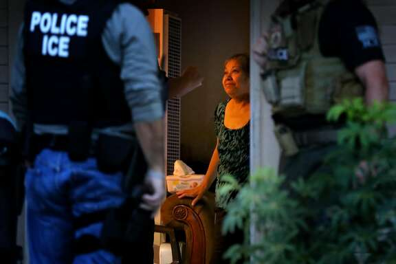 RIVERSIDE, CA - AUGUST 12: ICE Enforcement and Removal Operations officers, in search of 32-year-old Hugo Medina, question his mother Magdalena Medina, 69, about his whereabout in a morning raid on his residence in Riverside. Immigration and Customs Enforcement officials say they are relying more than ever on costly manhunts to locate immigrants in the country illegally who have criminal records. In the past, the agency would simply contact local jails where such immigrants were being detained and ask jail officials to hold them until an ICE van could pick them up, but hundreds of counties across the country stopped honoring such requests after a federal judge last year found that practice unconstitutional. (Irfan Khan/Los Angeles Times via Getty Images)