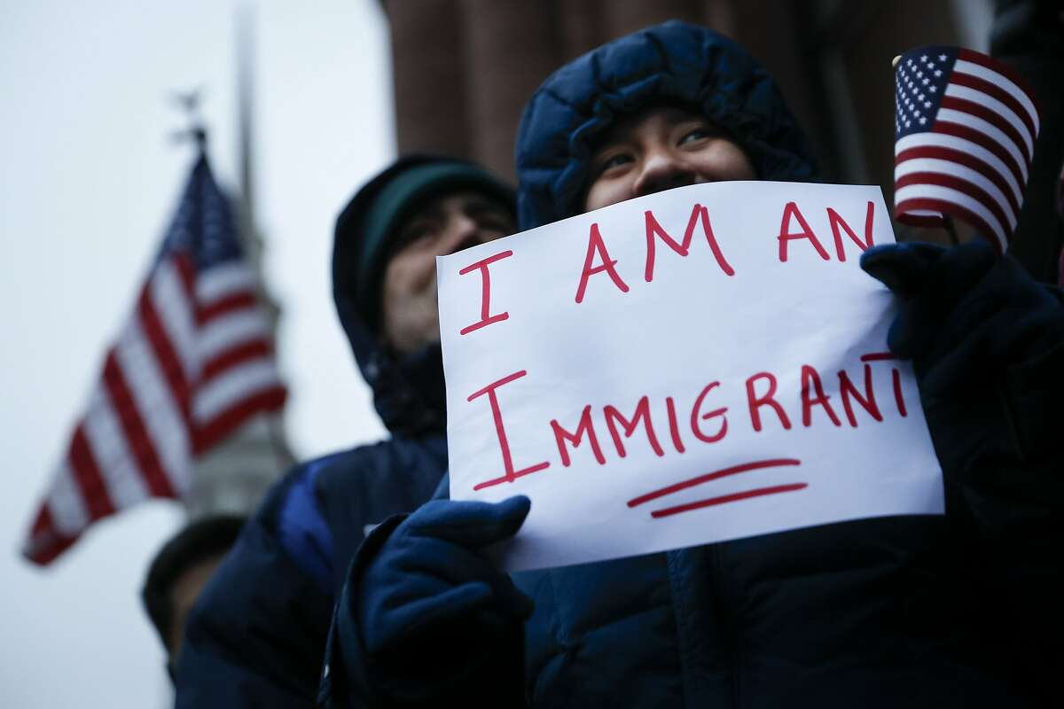 Demonstrators gather in solidarity against President Donald Trump's executive order temporarily banning immigrants from seven Muslim-majority countries from entering the U.S. and suspending the nation's refugee program Monday, Jan. 30, 2017, outside City Hall in Cincinnati. (AP Photo/John Minchillo)