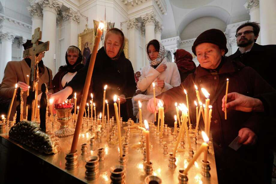 People light candles during a service Wednesday for victims of Monday's subway explosion in St.Petersburg, Russia. Investigators are searching for accomplices of the 22-year-old Kyrgyzstan native of identified as the suicide bomber. Photo: Dmitri Lovetsky, STF / Copyright 2017 The Associated Press. All rights reserved.