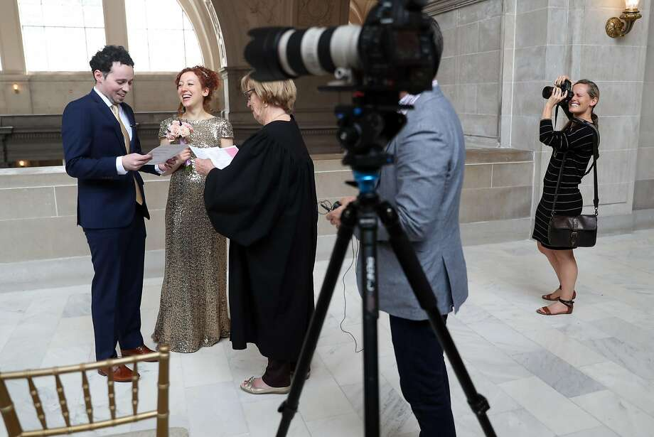 Photographer Jenny Morgan (right) documents the wedding ceremony of Mark Lyubovitsky and Mira Leytes at San Francisco City Hall. Morgan calls the city's new list an interference with her business. Photo: Scott Strazzante, The Chronicle