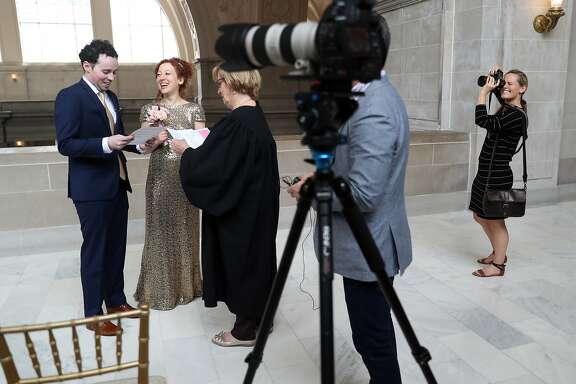 Wedding photographer Jenny Morgan documents the ceremony of Mark Lyubovitsky and Mira Leytes on the 4th floor of City Hall in San Francisco, Calif., on Wednesday, April 5, 2017.