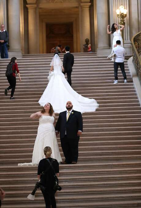 Wedding photographers work on the steps in the rotunda at City Hall before the new rules take effect. Photo: Scott Strazzante, The Chronicle