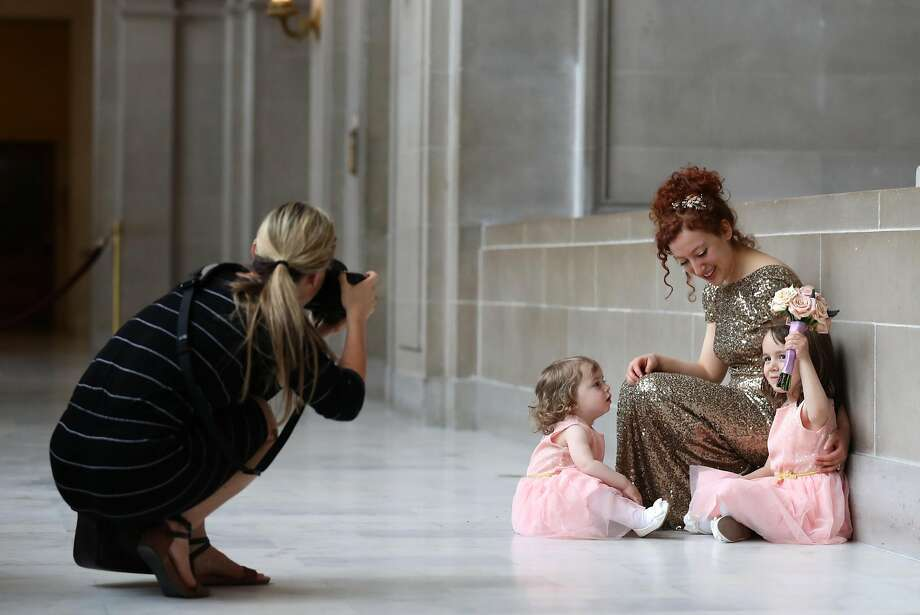 Wedding photographer Jenny Morgan, who opposes the new rules, takes pictures of bride Mira Leytes and her nieces, Lyael and Lila Subotnik, on the fourth floor of San Francisco City Hall. Photo: Scott Strazzante, The Chronicle
