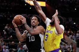 Los Angeles Lakers' LeBron James (23) drives between San Antonio Spurs' LaMarcus Aldridge (12) and Rudy Gay during the first half of an NBA basketball game Friday, Dec. 7, 2018, in San Antonio. (AP Photo/Darren Abate)