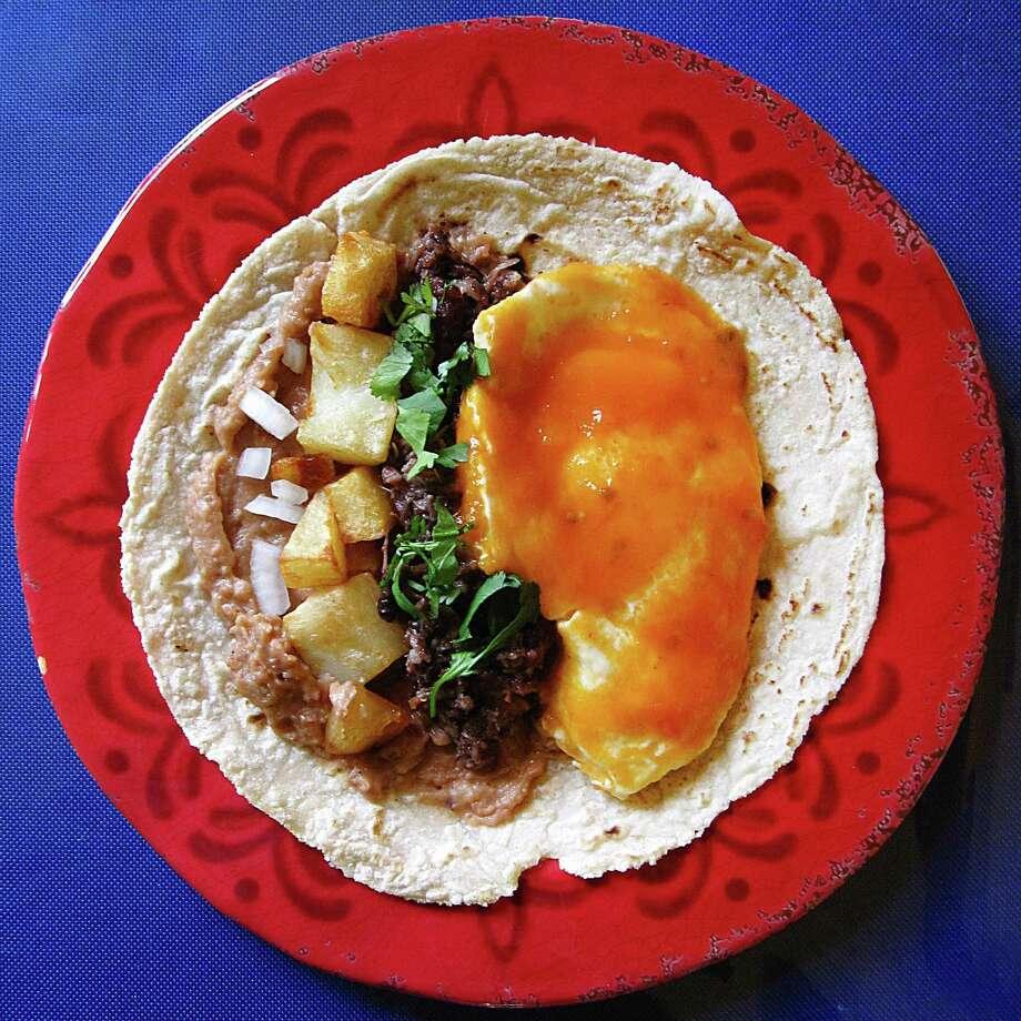 Huevos rancheros taco with barbacoa on a handmade corn tortilla from Taqueria Lupita on U.S. 181 South. Photo: Mike Sutter /San Antonio Express-News