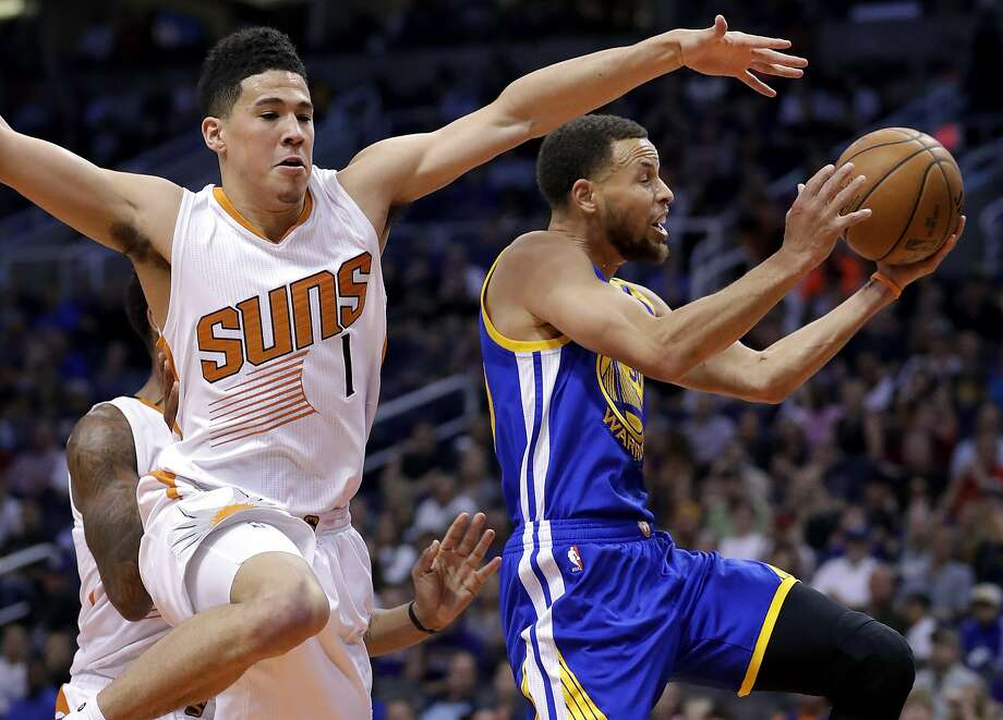 The Warriors' Stephen Curry drives past Suns' guard Devin Booker in the first half when a 23-point lead nearly vanished. Photo: Matt York, Associated Press