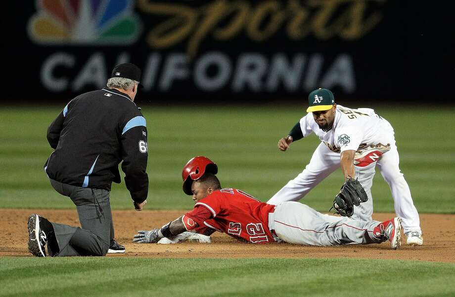 Marcus Semien (10) tries to apply the tag to Martin Maldonado (12) after Maldonado doubled in the second inning as the Oakland Athletics played the Anaheim Angels in Oakland, Calif., on Wednesday, April 5, 2017. Photo: Carlos Avila Gonzalez, The Chronicle