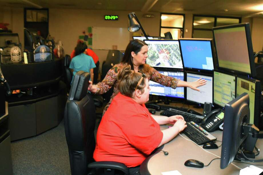 The Cypress Creek EMS Communications Center has updated all of its handheld radios in an effort to maximize efficiency between local emergency agencies. The move allows the center, which handles 911 and dispatch for 15 other emergency departments, to streamline communications in the field and helps cut costs for the six north Harris County fire departments that placed the new radio system on line last month. Communication manager Niky Smith, back, watches Alyssa Carl's  communication screen. Photo: Tony Gaines, Photographer