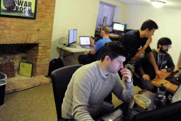 "Employees of software development and consulting company Jahnel Group work in the ""War Room"" of the company's office in Schenectady, N.Y. (Robert Downen/Times Union)"