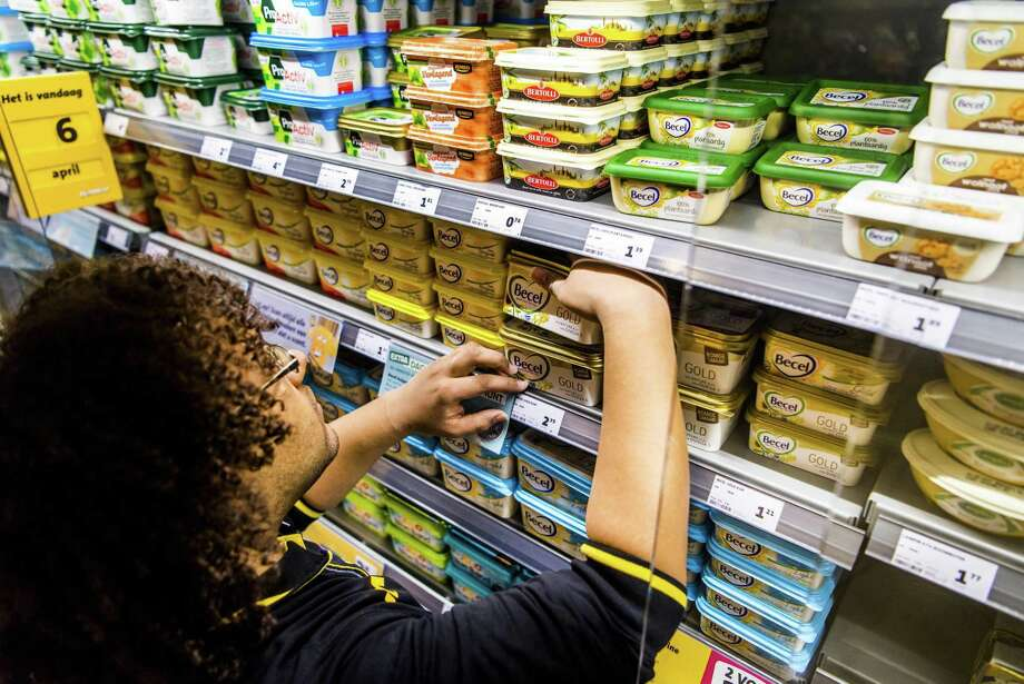 An employee arranges some of Unilever's margarine brands. The spreads business, which includes the margarine brands Country Crock, Flora and I Can't Believe It's Not Butter, was merged two years ago with a baking and cooking segment in Unilever's foods division. The company says it will seek to sell or separate the business. Photo: Marco De Swart /AFP /Getty Images / AFP